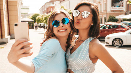 Two-young-beautiful-smiling-hipster-girls-trendy-summer-clothes-sexy-carefree-women-posing-street-background-sunglasses-they-taking-selfie-self-portrait-photos-smartphone-sunset_158538-15920_thumb_main